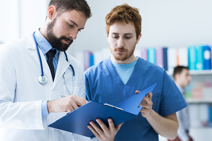 male doctor and medical assistant checking paperwork