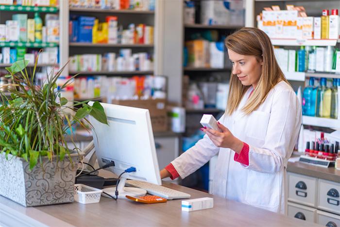 female pharmacist holding medication at pharmacy counter
