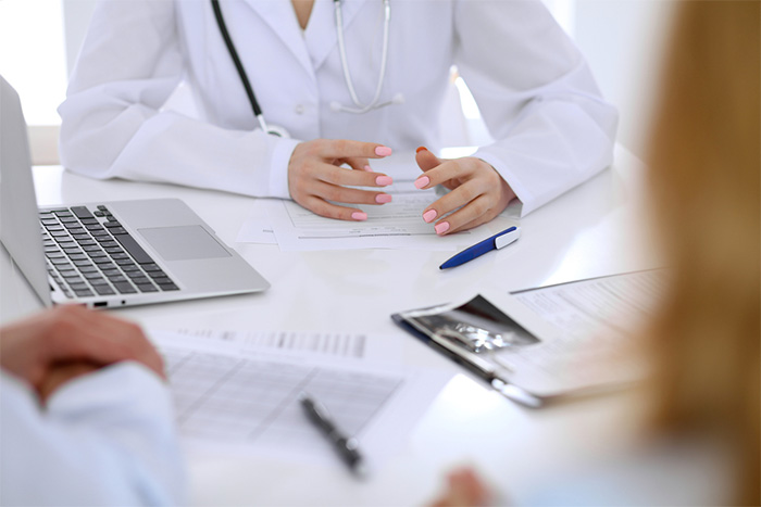 nurse in white lab coat talking with patients