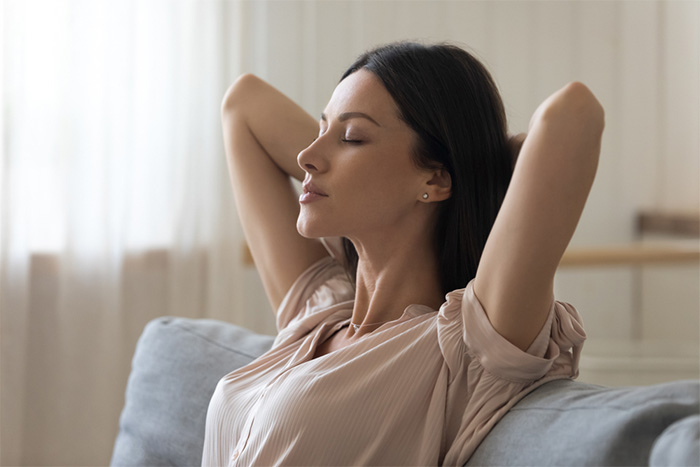 tired woman resting eyes on couch