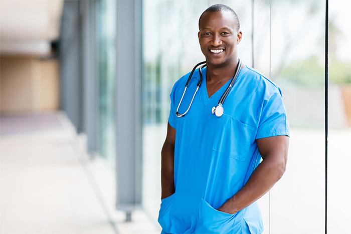 smiling male surgeon wearing scrubs