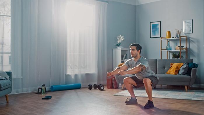 man doing squats at home
