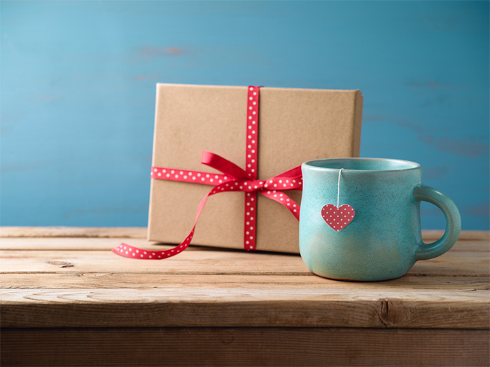 wrapped gift and cup of tea on wooden table