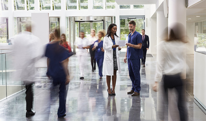 doctor and nurse talking in crowded lobby