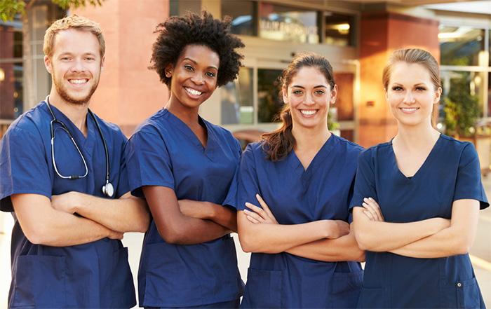 group of registered nurses smiling outsiden