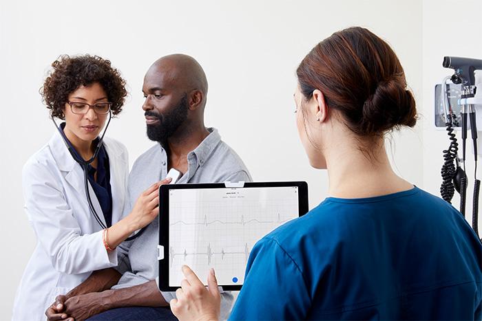 clinician using eko duo stethoscope with earpiece on male patient