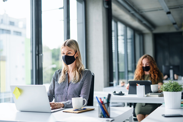 young female professionals wearing face masks at work