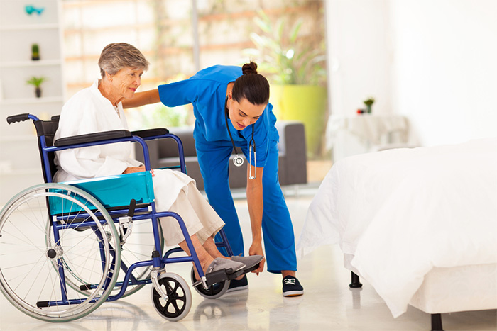 caergiver helping elderly woman in a wheelchair