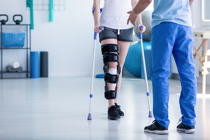 physical therapy assistant supporting patient with leg injury
